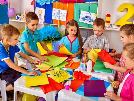 Grupowe dzieciaki w szkole podstawowej robią coś z kolorowego papieru.