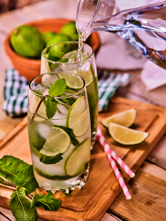 Country drink. Pouring from jug of cocktail drink on wooden boards with lime and mint . Drink number seventy three with mohito cocktail and ice cubes . Country life. Light background. Reklamní fotografie