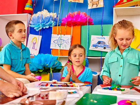 Muffa dei bambini del gruppo dalla plastilina nell'asilo. Ragazza e ragazzi si modellano insieme dalla plastilina nella scuola primaria.