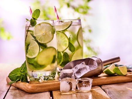 mohito: Alcohol drink. On wooden boards two glasses with alcohol drink and ice cubes. A drink number hundred fifty eight cocktail mohito and scoop ice with straw. Country still life outdoor. Light background. Stock Photo
