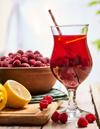 raspberries: On wooden boards is ice cold beverage two glasses with raspberry lemon cocktail . Alcohol country cocktail beverage number hundred seventy three with raspberry clay bowl on checkered napkin outdoor . Stock Photo