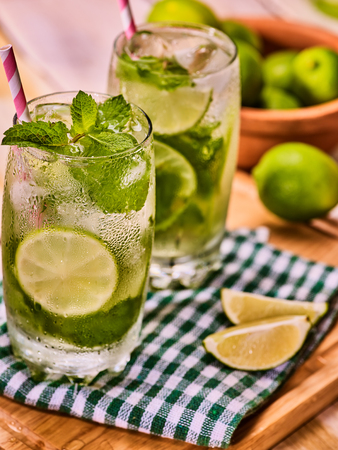 country life: Alcohol drink. On wooden boards two glasses with alcohol drink and ice cubes. Drink hundred sixty three cocktail mohito with straw and lime and mint on checkered cloth. Country life. Light background.