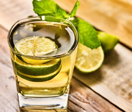 country life: Alcohol cocktail. On wooden boards is glass with alcohol green transparent drink. A drink number hundred sixty four mohito cocktail with lime. Close up of country life. Stock Photo