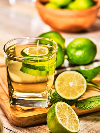 country life: Country drink. On wooden boards is glass with green transparent drink and lime glue bowl. A drink number hundred sixty six mojito with mint leaf on sunlight . Country life. Vertical still life.