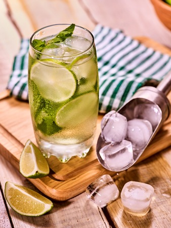 country life: Alcohol cocktail. On wooden boards is glass with alcohol cocktail and ice cubes. A drink number hundred sixty eight cocktail mohito and scoop ice . Country life. Outdoor. Stock Photo