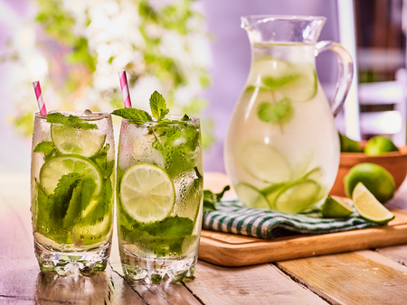 country life: Country drink. On wooden boards is glass jug and two glasse with transparent drink and lime glue bowl. A drink number hundred seventy three with ice cubes . Country life. Light background.