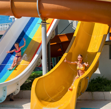 water   slide: Two happy children on water slide at aquapark and thumb up. Summer holiday. There are two water slides in water park. Outdoor summer holiday.