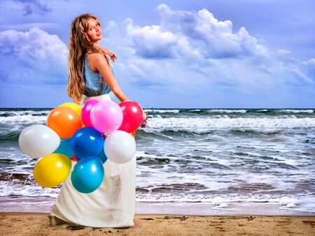 carelessness: Girl keeps colored balloons walk on sea beach. There waves on sea beach.