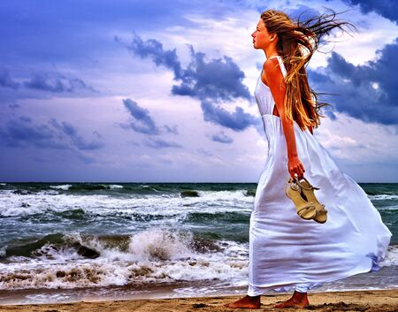 bare foot girl: Summer girl sea. Bare foot girl goes on sea coast. Beautiful sea landscape.