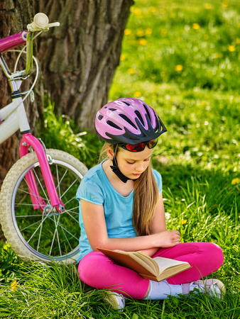 Bikes cycling kid girl. Child girl rides bicycle. Bicycling girl reading book near bicycle into park outdoor. Cycling is good for health. Cyclist wearing helmet looking at book.
