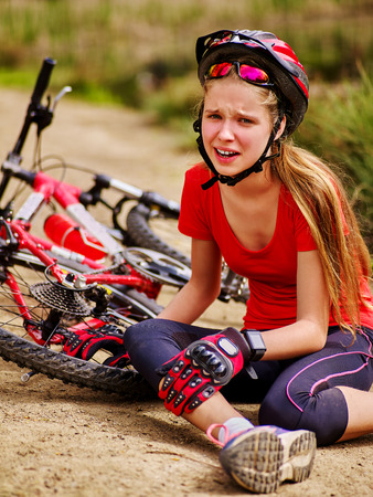 Bikes cycling girl. Girl rides bicycle. Girl girl fell off bike. Cyclist girl keeps self for bruised knee. Girl is crying sitting on road.
