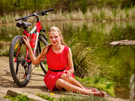 ecotourism: Bikes cycling girl. Girl wearing red polka dots dress rides bicycle into park. Girl in ecotourism. Girl sits on shore river water.