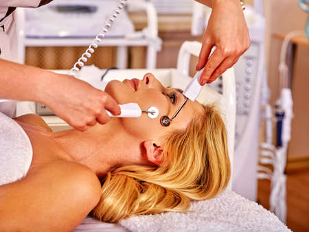 Young woman receiving electric galvanic face spa massage at beauty salon. Anti-aging facial massage. Stock Photo