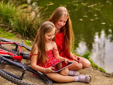 lunares rojos: Bicicletas Ciclo de la muchacha. La muchacha que desgastan los lunares rojos visten de recreación cerca de la bicicleta en el parque. Los niños ven Tablet PC. Chica en el ecoturismo.