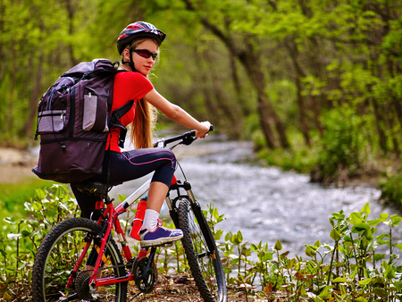 rucksack ': Bicycle girl. Girl with big rucksack rides bicycle. Girl cycling fording throught water . Cycling trip is good for health. Cyclist turned back.