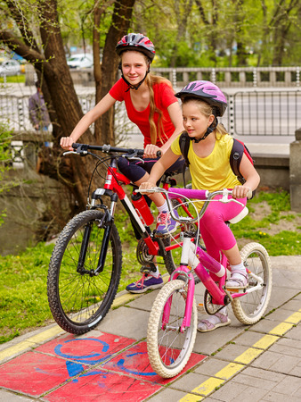 shared sharing: Children girls wearing bicycle helmet with rucksack ciclyng bicycle. Girls children cycling on yellow bike lane. Bike share program save money and time. City trip. Stock Photo