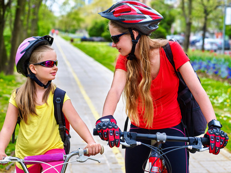 bike lane: Girls wearing bicycle helmet and glass with rucksack ciclyng bicycle. Girls children cycling on yellow bike lane. Bike share program save money and time at city street. Girls talking to each other.