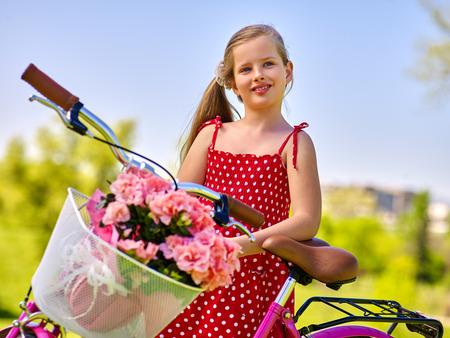 lunares rojos: Retrato de ni�a en bicicleta. La muchacha del ni�o que lleva lunares rojos vestido de paseos en bicicleta con flores canasta. cielo azul en el fondo del parque de verano.