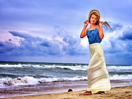 strong wind: Summer girl sea. Girl on beach near ocean with waves. Girl keeps her hat. Strong wind and waves on sea beach. Stock Photo
