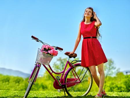 lunares rojos: hermosa chica delgada vestida de lunares rojos alineada que mira para arriba en el cielo azul y mantiene la bicicleta con flores canasta. Estilo rústico.