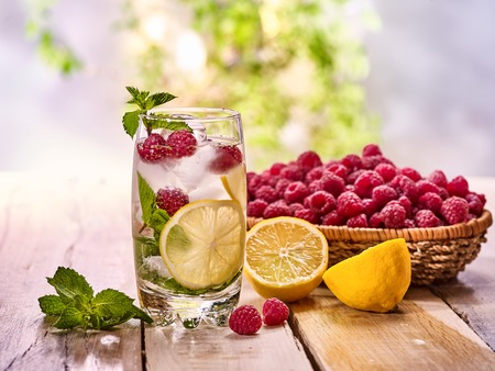 country life: On wooden boards glass with raspberry alcohol cocktail and ice cubes. Cocktail number hundred and ninety six cocktail raspberry mojito with raspberry basket. Country life. Outdoor background. Stock Photo