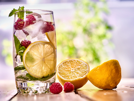 country life: Alcohol cocktail. On wooden boards is glass with alcohol cocktail and ice cubes. Drink number hundred ninety five cocktail raspberry mojito and half lemon with mint. Country life. Outdoor background. Stock Photo