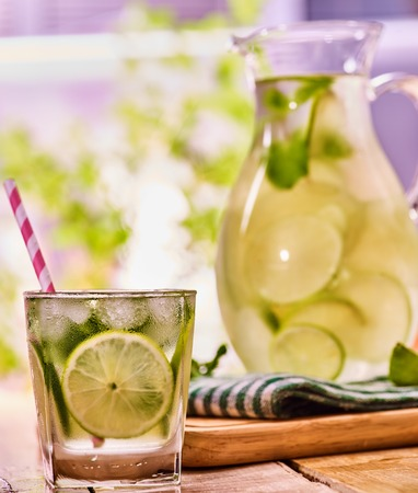 country life: Country drink. On wooden boards is glass jug and glass with transparent drink and lime . A drink number hundred and ninety four with ice cubes . Country life. Light background. Stock Photo