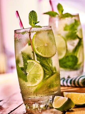 country life: Alcohol cocktail. On wooden boards couple of glasses with alcohol cocktail and ice cubes. A cocktail number hundred and ninety three cocktail mohito with mint leaf. Country life. Light background. Stock Photo
