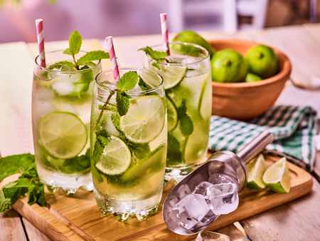 country life: Alcohol cocktail. On wooden boards three glasses with alcohol cocktail and ice cubes. Drink number hundred and ninety two cocktail mohito with straw and lime and mint leaf. Country life. Indoor.