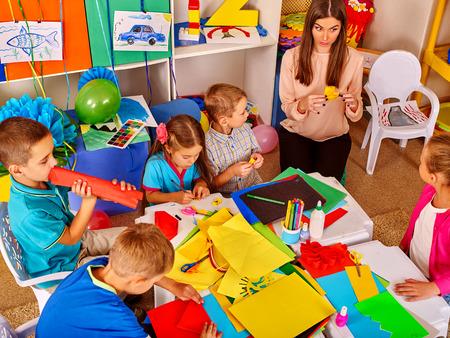 Niños con el profesor están haciendo algo fuera de papel de colores sobre la mesa en la escuela primaria. lección, los niños de artesanía en la escuela primaria.