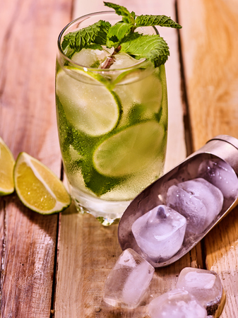 twenty one: Alcohol drink. On wooden boards is glass with alcohol drink and ice cubes. A drink number two hundred twenty one cocktail mohito and scoop ice . Country life still life . Wooden boards background. Stock Photo
