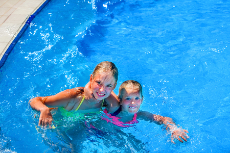 aquapark: Two nice children hugging and looking up swim in swimming pool. Summer swimming holiday. Outdoor swimming pool. Children activities lifestyle. Blue water in swimming pool.