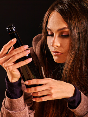 dipsomania: Drunk girl holding bottle of alcohol. Soccial issue alcoholism. Alcohol bottle in hands of drunk girl. Stock Photo