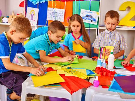 niño escuela: Los niños están haciendo algo fuera de papel de colores sobre la mesa en la escuela primaria. lección, los niños de artesanía en la escuela primaria. los niños de desarrollo de artesanía en clase en la escuela.