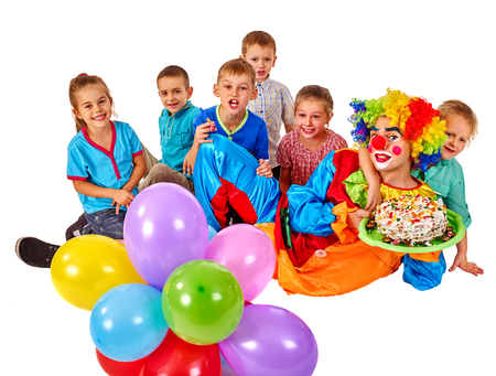 children birthday: Clown keeps bunch of balloons and birthday cake with group children. Birthday celebration. Isolated. Stock Photo