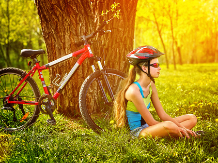 Bikes cycling girl. Girl rides bicycle. Girl in cycling have rest sitting under tree. Bicycling is good for health. Bicyclist looking at faraway on sunset.