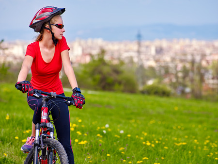 bicycling: Bicycle girl. Girl rides bicycle into city. Girl in bicycling. Bicycling is good for health. Bicycle girl is looking at city in faraway.