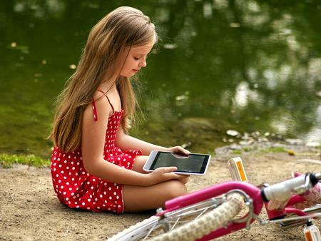 red polka dots: Bicicleta niña. La muchacha que desgastan los lunares rojos visten de recreación cerca de la bicicleta en el parque. Los niños ven Tablet PC. Chica en el ecoturismo. Muchacha cerca del río. Foto de archivo