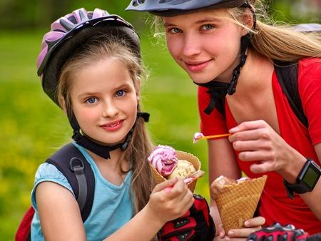 niña comiendo: Dos bicicletas chica ciclista. Chicas con casco de bicicleta con paseos en bicicleta mochila. niños de las muchachas se montan en bicicleta en el parque de verano. niñas felices bicicleta Ciclismo de comer cono de helado.