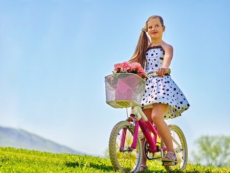blu sky: Nice girl ride on bicycle . Child girl wearing white polka dots dress rides bicycle with pink flowers basket. Green grass and blu sky on summer park background.