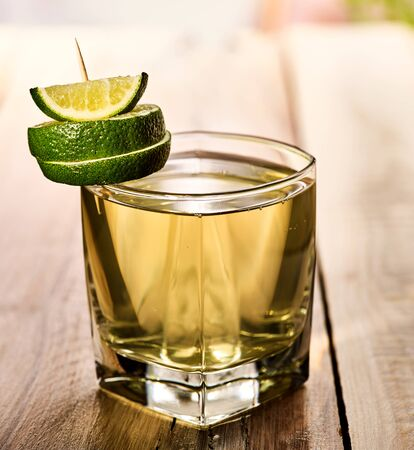 country life: Healthy drink. On wooden boards is glass with green transparent drink. Drink number two hundred sixty-seven cold green tea with lime. Country life. Light background. Single lime glass.