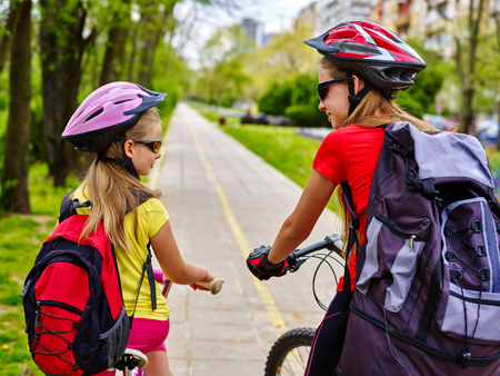 bike lane: Bikes bicyclist girl. Girls wearing bicycle helmet and rucksack ciclyng bicycle. Girls children cycling on yellow bike lane. Bike share program. Back view. Bicycle girl speaking.