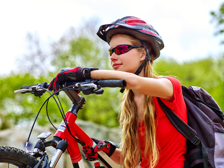 faraway: Bikes bicyclist girl. Girl rides bicycle into mountains. Girl on bicycle in mountaineering . Girl carries her bike over rocks. Bicyclist looks forward faraway. Stock Photo