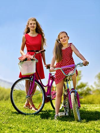 lunares rojos: Bicicletas chica bicicleta. Muchacha del adolescente y el ni�o con vestido de lunares rojo mantiene bicicleta con flores canasta. verano al aire libre en el parque. cielo azul aganist.