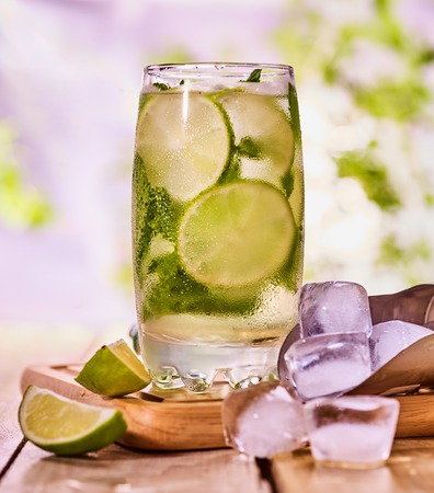 country life: Alcohol cocktail. Wooden boards is glass with alcohol drink and ice cubes. Drink number two hundred fifty nine cocktail mohito and scoop ice . Country life cocktail . Summer outdoor. Light background. Stock Photo
