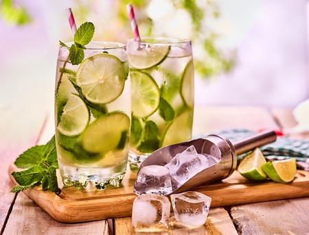 country life: Alcohol drink. Wooden boards are glass with alcohol drink and ice cubes. A drink number two hundred and sixty cocktail mohito and scoop ice . Country life cocktail on country table. Light background. Stock Photo