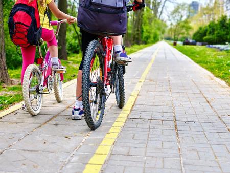 ciclismo: chica de la bicicleta. Las piernas de la chica de la bicicleta. muchachas de los niños en bicicleta en el carril bici amarilla. programa de participación en bicicleta ahorrar dinero y tiempo en la calle de la ciudad. Vista trasera. concepto de deporte de la bicicleta.