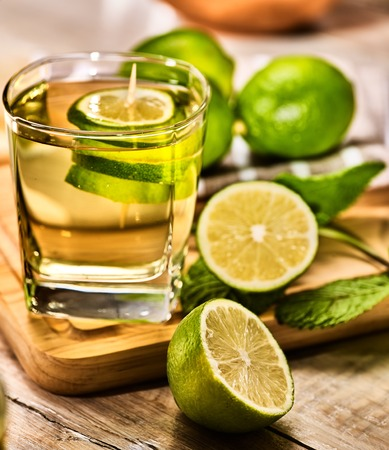 country life: On wooden boards glass with alcohol green mohito drink. A mint drink number three hundred and nineteen mojito cocktail with half lime . Country life. Light background. Stock Photo