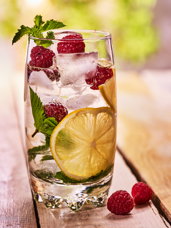 Alcohol drink. On wooden boards is glass with alcohol drink and ice cubes. A drink three hundred two cocktail raspberry mojito and some slice lime with mint. Country life. Outdoor. Light background. Stock Photo