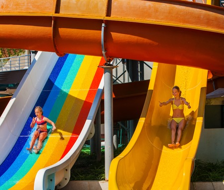 water   slide: Two children on water slide at water park thumb up. Outdoor park. Stock Photo